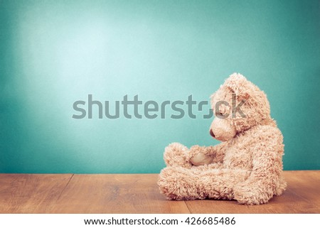 Teddy Bear retro old toy siting alone front mint green background. Vintage style filtered photo - stock photo