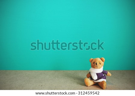 Teddy bear retro toy on table front mint green background. Vintage effect. - stock photo