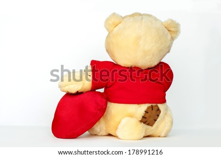 Teddy Bear sitting back side and holding a red heart on white background - stock photo