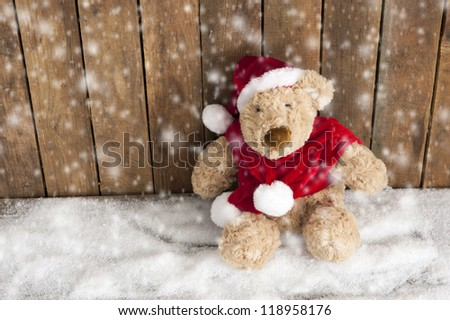 Teddy bear sitting in the snow - stock photo