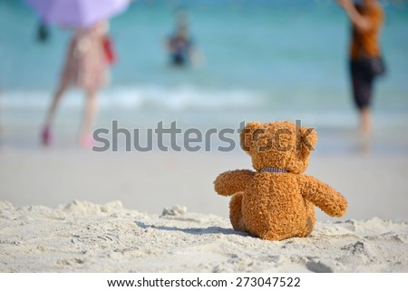 Teddy Bear sitting on the beach with blue sea and sky background. Concept about loneliness and expectancy. - stock photo