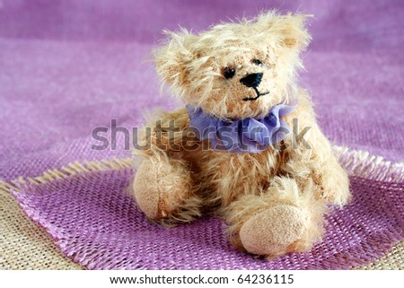Teddy bear, soft and handmade, sitting on colored hessian - stock photo