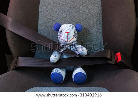 Teddy bear strapped in with seat belt in a car - stock photo