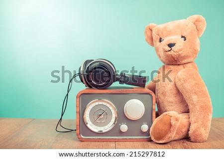Teddy Bear toy, retro radio, headphones front mint green background - stock photo