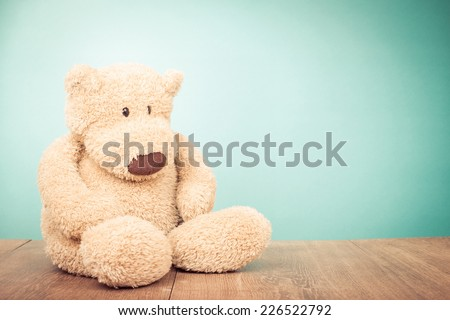 Teddy Bear toy sitting alone front mint green background - stock photo