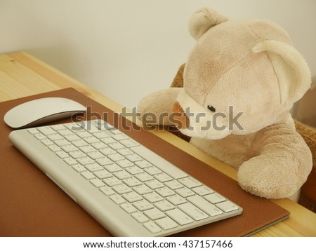 Teddy Bear toy with computer keyboard  - stock photo