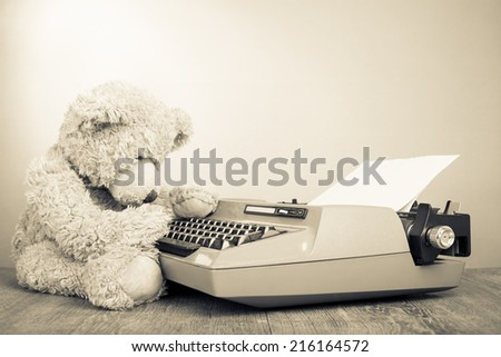 Teddy Bear toy with retro typewriter. Vintage old style sepia photography - stock photo