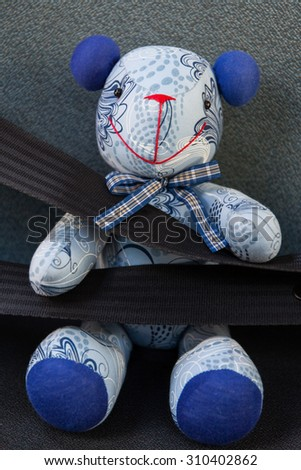 Teddy bear toy with seat belt fastened - stock photo