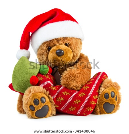 Teddy bear wearing a santa hat with christmas stocking isolated on white background - stock photo