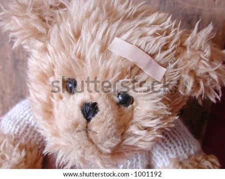 teddy bear with adhesive bandaid on forehead - stock photo