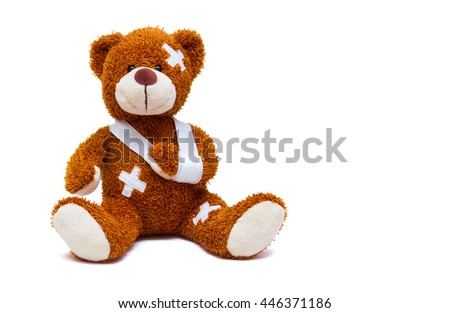 Teddy bear with bandages and broken hand isolated on white background - stock photo