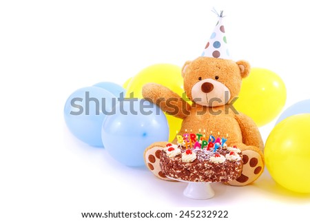 Teddy bear with birthday cap, balloons and cake with candles. Birthday greeting card, isolated, with copy space. Happy birthday cake with burning candles. - stock photo