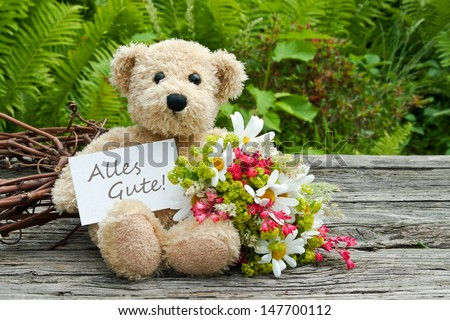teddy bear with flowers and card with lettering all the best/all the best/teddy - stock photo