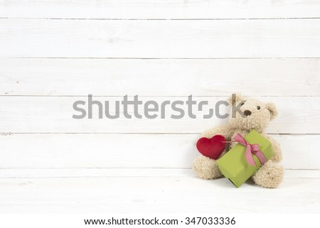 teddy bear with gift on white wooden background