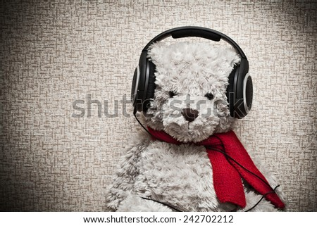 Teddy bear with headphones and a red scarf - stock photo
