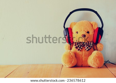 teddy bear with headphones over wooden table - stock photo