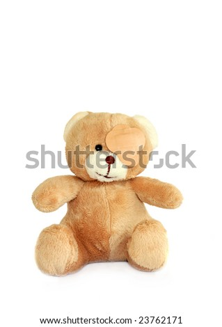 Teddy bear with plasters on its eye, over white. - stock photo