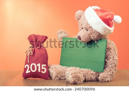 Teddy Bear with Santa hat, gift bag, signboard for New Year greeting card background - stock photo
