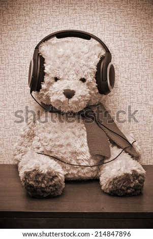 Teddy bear with scarf listening to music on headphones. Photo by sepia toned - stock photo