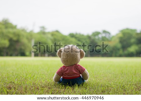 Teddy bears sitting on l garden with lens flare on blurred background ,Concept loneliness.copy space.