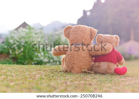 Teddy bears sitting on the beautiful garden with love. Concept about love and relationship - stock photo