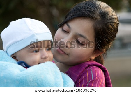 teen age girl holding her new born baby brother in lap - stock photo