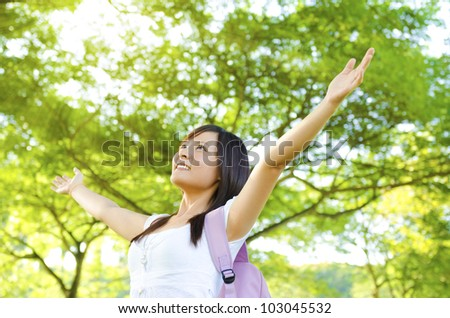 Teen arms raised enjoying the fresh air in green forest. - stock photo