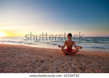 Teen boy at the beach meditating on sunset