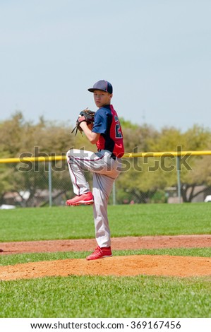 Teen boy baseball pitcher about to throw a pitch. - stock photo