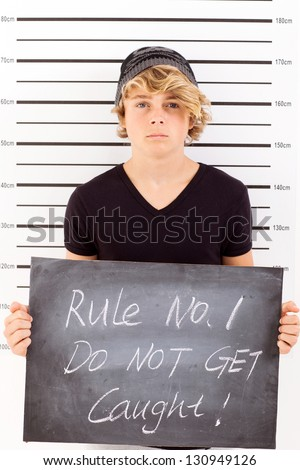 teen boy holding a blackboard criminal mug shot - stock photo