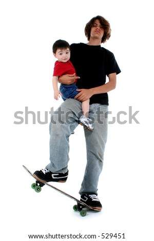 Teen boy holding toddler boy while standing on skateboard. Shot in studio over white.