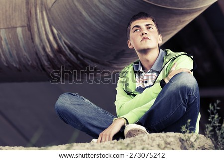 Teen boy in depression sitting on the ground - stock photo