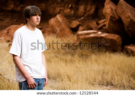 teen boy in Wyoming wilderness area, large red-brown boulders in background, copyspace