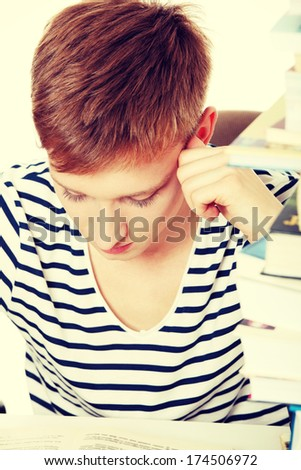 Teen boy learning at the desk, isolated on white  - stock photo