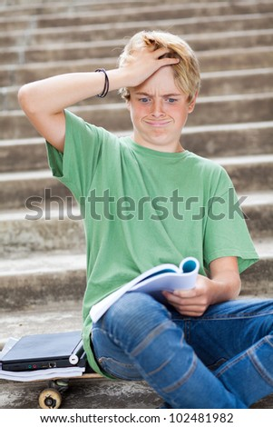 teen boy looking frustrated while reading a book - stock photo