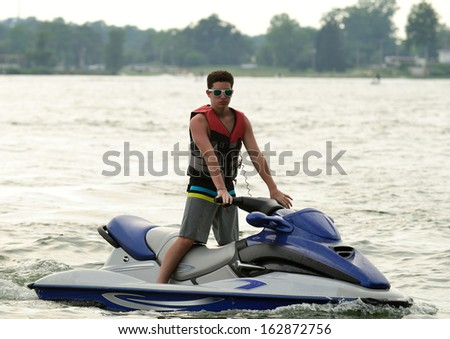 Teen boy on personal watercraft on a lake.