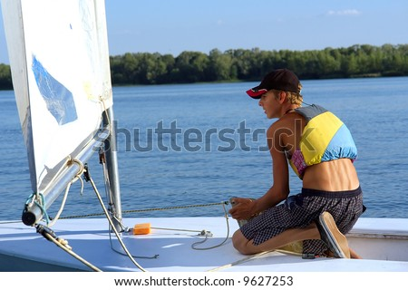 Teen boy pulls up sail of the yacht on river. Shot in July, Dnieper river, Ukraine.
