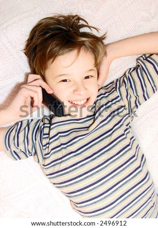 Teen boy relax by talking on cell phone - stock photo