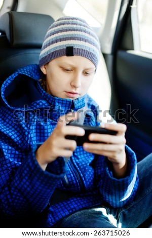 teen boy sitting in the car with phone - stock photo