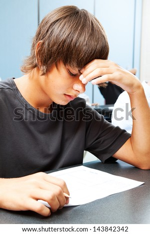 Teen boy taking an objective test in school and worried about the outcome.
