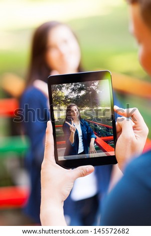 teen boy taking photos of his girlfriend using a tablet computer - stock photo
