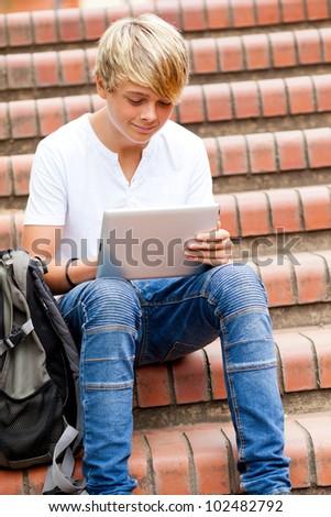 teen boy using tablet computer outdoors - stock photo
