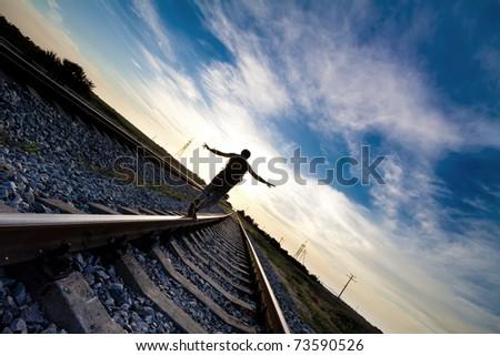 Teen boy walking on rail road - stock photo