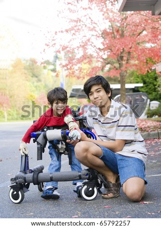 Teen boy with disabled little brother in walker out walking