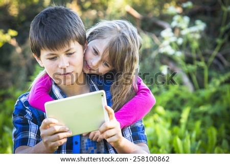 Teen boy with his younger sister sitting in a Park and using the tablet. - stock photo