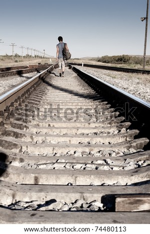 Teen boy with problem walking on railroad - stock photo
