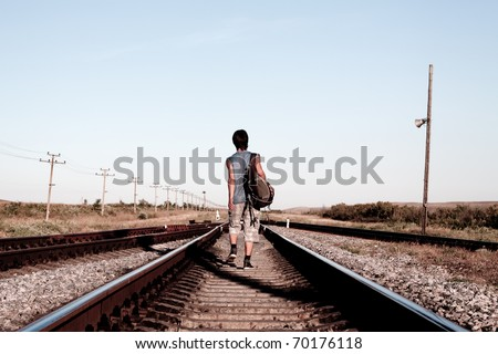 Teen boy with problems walking on rail road - stock photo