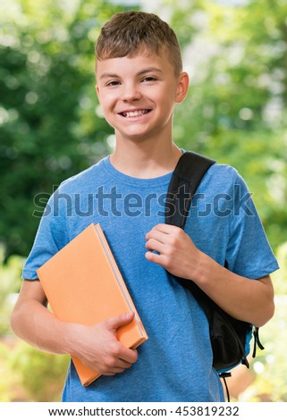 Teen boy 12-14 year old with schoolbag and book posing outdoors. - stock photo