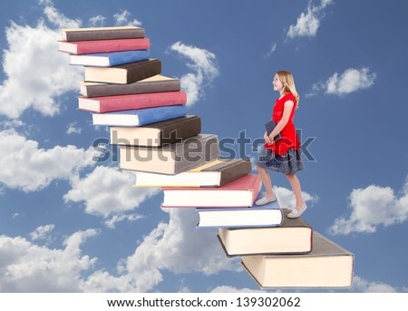 teen climbing a staircase of books, on a blue sky background - stock photo