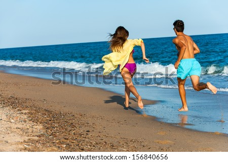 teen couple chasing each other on beach. - stock photo